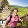 Happy asian senior couple hiking in the mountain - Foto Stock