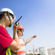 Two refinery workers looking the large refinery background — Stock Photo