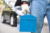 Car mechanic holding toolbox and standing before vehicle — Stock Photo