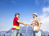 Two engineers handshaking before large solar power station — Stock Photo