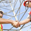 Two power line tower workers with handshaking — Stock Photo