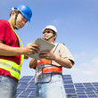 Stock Photo: Two workers discussing with tablet pc before solar power stat