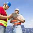 Two workers discussing with tablet pc before solar power stat — Stock Photo #15519785
