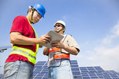 Two workers discussing with tablet pc before solar power stat — Stock Photo
