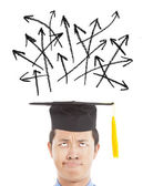 Confused graduate looking many different direction arrow sign — Stock Photo