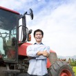 Happy middle aged asian farmer with old tractor - Stockfoto