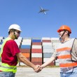 Two happy workers handshaking before transportation containers — Stock Photo