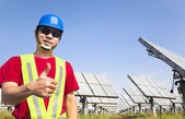 Happy worker with thumb up and standing before solar panel track — Stock Photo