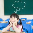 Little girl in the classroom with thinking cloud symbol - Stock Photo
