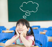 Little girl in the classroom with thinking cloud symbol — Stock Photo