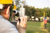 Inżynier geodeta z partnerem, co środek na polu — Zdjęcie stockowe