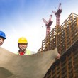 Two construction workers with giant cranes and building — Stock Photo