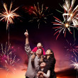 Happy family looking fireworks in the evening sky — 图库照片