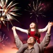 Father and daughter looking fireworks in the evening sky — Stock Photo