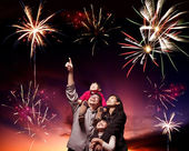 Happy family looking fireworks in the evening sky — Stock Photo