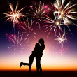 Happy young couple with fireworks background — Stock Photo