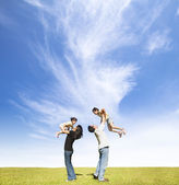 Happy family on the grass with cloud background — Stock Photo