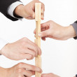 Hands of business group building by wooden block — Stock Photo #19564619