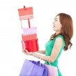 Surprised young woman holding gift box and shopping bag — Stock Photo
