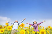 Relaxed senior couple standing in the sunflower garden — Stock Photo