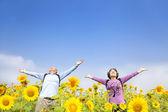 Relaxed senior couple standing in the sunflower garden — Stock Photo