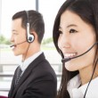 Smiling asian businessman with call center agent - Stock Photo