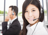 Beautiful smiling businessman with call center agent — Stock Photo