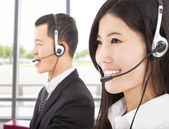 Smiling asian businessman with call center agent — Stock Photo