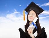 Sonriente mujer graduada sostiene grado con el fondo de nube — Foto de Stock