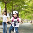 Happy little girl riding bicycle go to school - Stockfoto