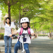 Happy little girl riding bicycle go to school - Stock Photo