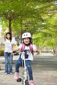 Glückliche kleine mädchen reiten fahrrad zur schule gehen — Stockfoto