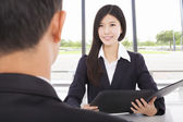 Smiling businesswoman interviewing with businessman in office — Photo