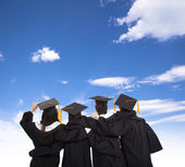Four graduate students looking at sky — Stockfoto