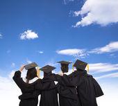 Vier afgestudeerde studenten kijken naar sky — Stockfoto
