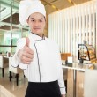 Young chef with thumb up gesture in the restaurant — Stock Photo