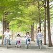 Happy family riding bicycle in the park — Foto de Stock