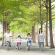 Happy family riding bicycle in the park — 图库照片