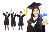 Happy graduate girl and students — Stock Photo