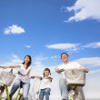Happy family riding bicycle with cloud background — Stock Photo #23904127