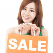 Happy woman showing shopping bag with sale written — Stock Photo