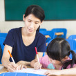 Mother teaching little girl drawing picture in the classroom — Foto Stock