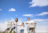 Happy family riding bicycle with cloud background — Stock Photo