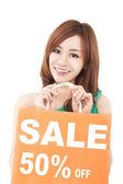 Szczęśliwa kobieta pokazano torba na zakupy z sprzedaż napisał — Zdjęcie stockowe