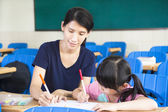 Mother teaching little girl drawing picture in the classroom — Stockfoto