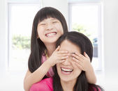 Happy little girl cover her mother eyes for fun — Stock Photo