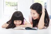 Joven madre y su hija se encuentran en el piso y leyendo un bo — Foto de Stock