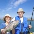 Happy senior couple go fishing and showing big fish — Stock Photo