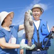 Happy asian senior couple fishing and showing big grouper — Stock Photo