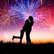 Loving young couple with fireworks background — Stock Photo